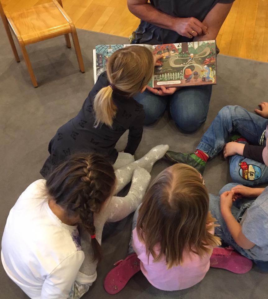 Eine Person kniet am Boden und hält das aufgeschlagene Kinderbucht. Rund herum sitzen fünf Kinder. Ein Mädchen beugt sich nach vorne und zeigt auf das Buch.