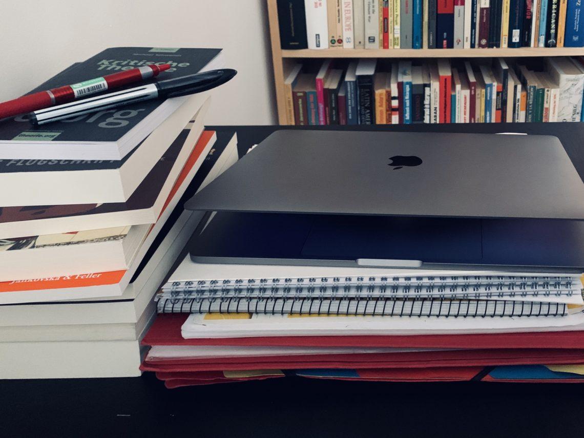 Im Hintergrund sieht man ein Bücherregal. Davor einen Stabelbücher. Darauf liegen zwei Stifte. Neben dem Bücherstapel liegt ein Stapel mit Maßen und Hefte. Darauf liegt ein leicht aufgeklapptes Laptop.