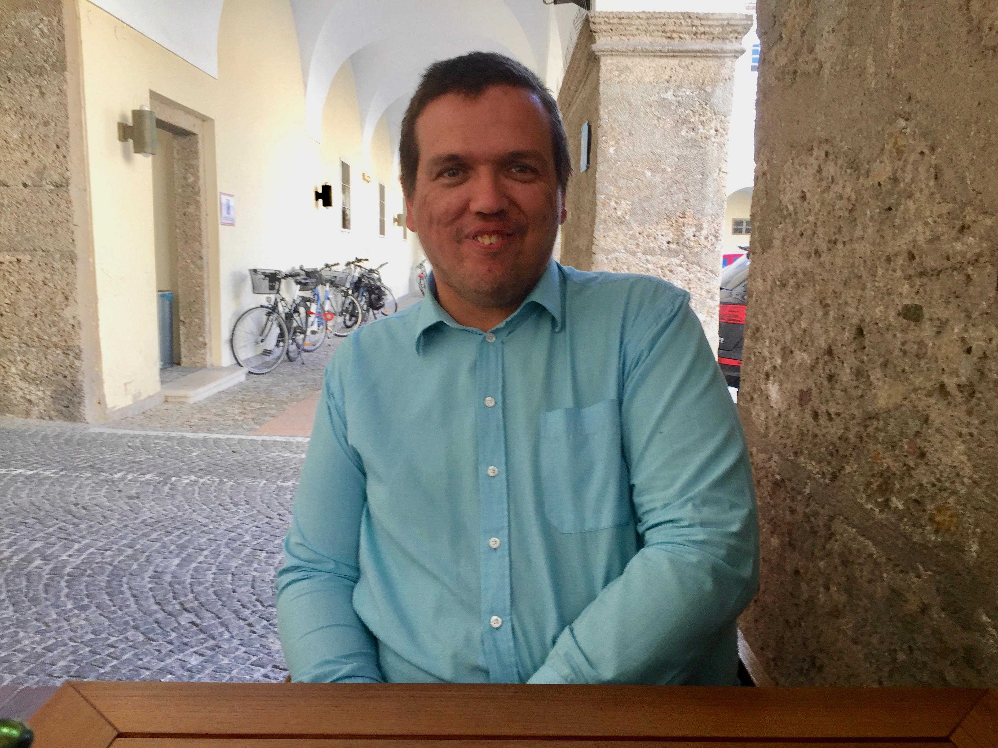 Erich Girlek sitzt an einem Tisch. Er lächelt. Er trägt ein hellblaues Hemd und einen Kurzhaarschnitt.