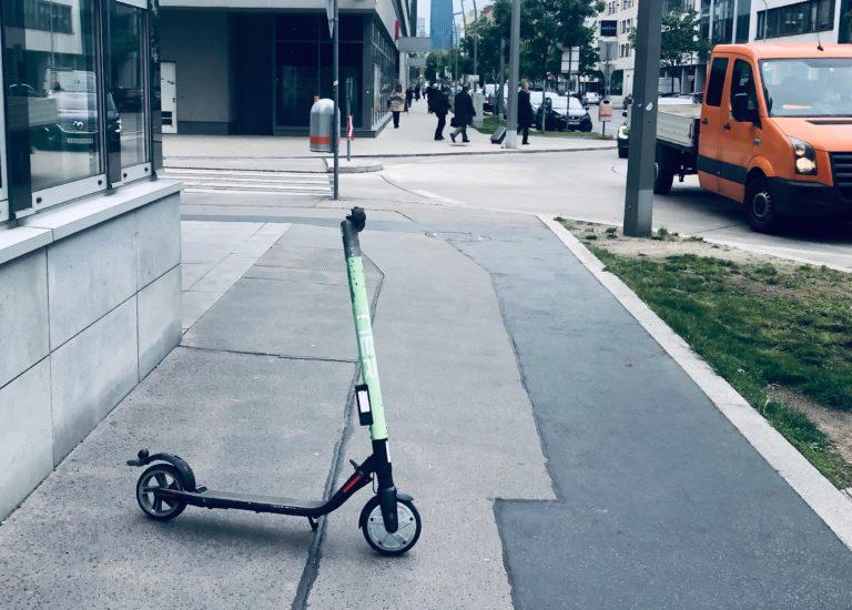 Ein E-Scooter steht quer über den Gehsteig.