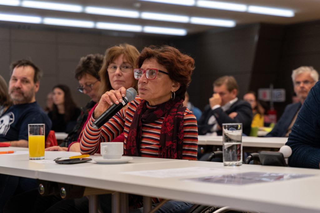 Eine Teilnehmerin mit kurzen Haaren und roter Brille spricht ins Mikrofon.