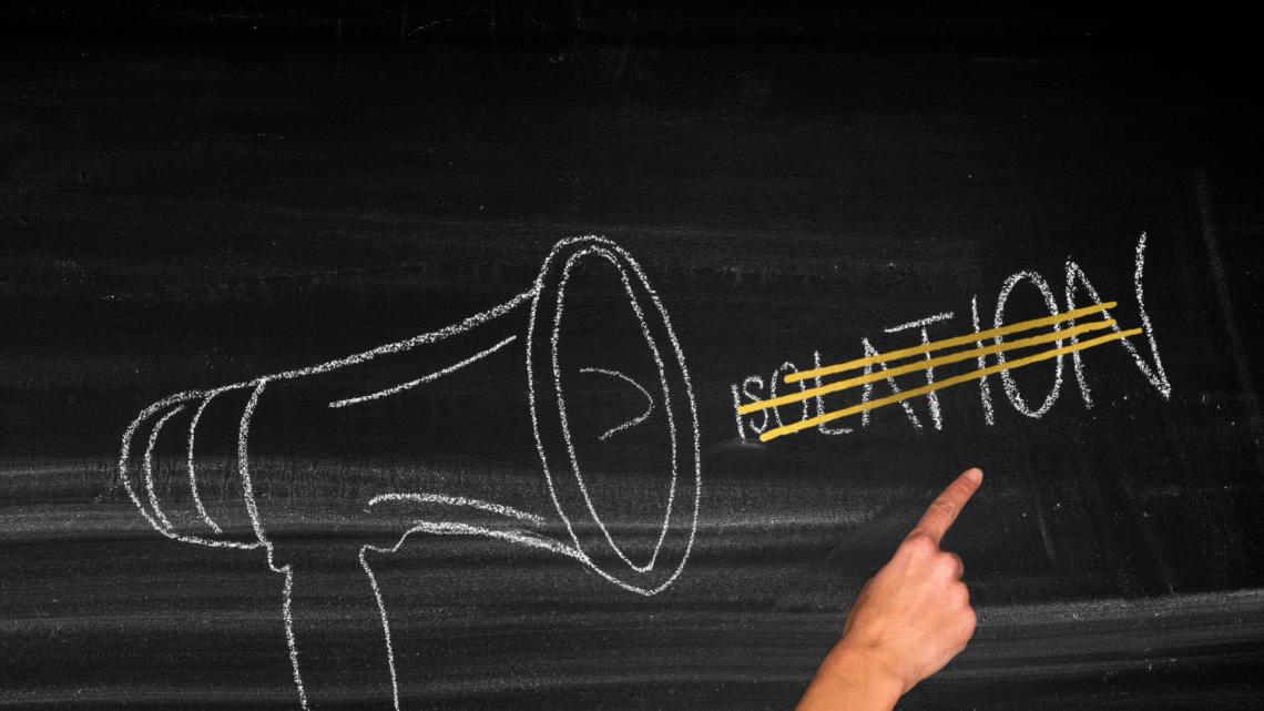 Auf einer Tafel ist mit Kreise ein Megaphon gezeichnete. Rechts daneben steht das Wort Isolation. Die Buchstanden fangen klein an und werden immer größer. Das Wort Isolation ist gelb durchgestrichen.