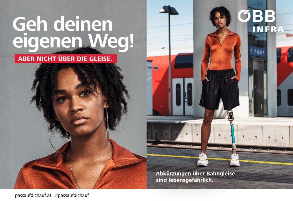 Eine junge, selbstbewusste Frau steht mit dem Rücken zum Bahngleis. Ihre Hände hat sie lässig in die Hosentaschen gesteckt. Sie trägt kurze sportliche Shorts, modische weiße Turnschuhe und außerdem eine Beinprothese.