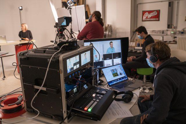 Hinter den Kulissen. Man sieht viele Bildschirme und Kameras. Einige Menschen arbeiten an der technischen Umsetzung.