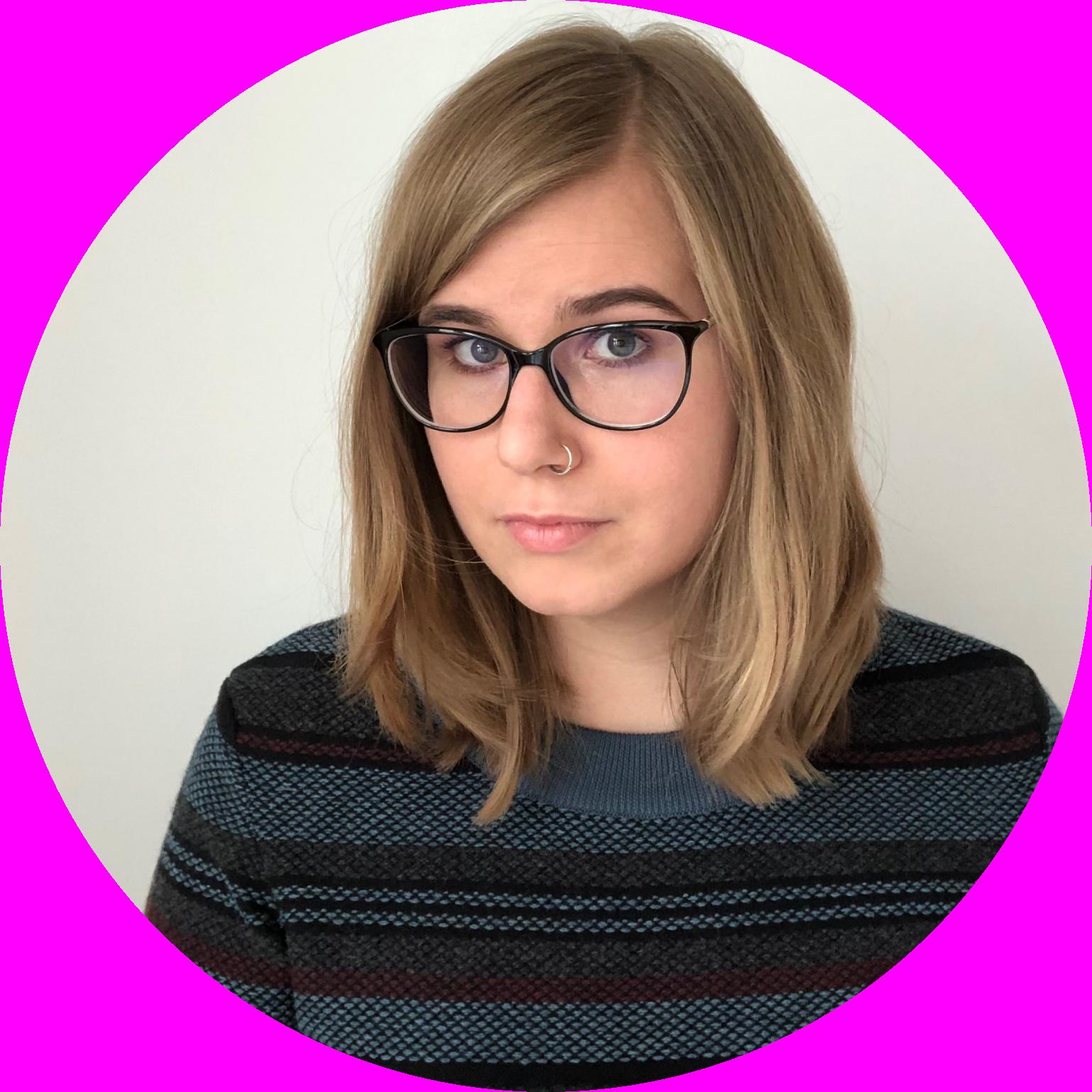 Portraitfoto von mir. Ich trage eine schwarze Brille, einen Nasenring, einen dunklen, gestreiften Pullover und offene, mittellange, blonde Haare.