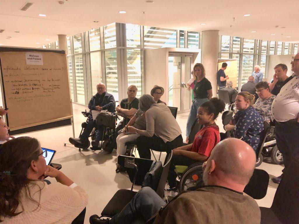 Das Publikum sitzt um ein Flipchart und diskutiert.