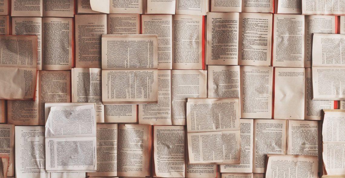 Man sieht zahlreiche aufgeschlagene Bücher nebeneinander liegen. Manche aufrecht, manche gedreht.