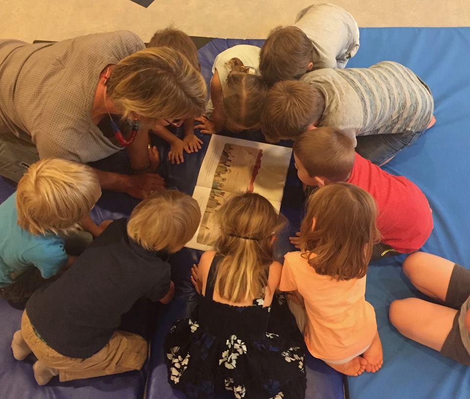 Die Kinder sitzen im Kreis um das Buch.