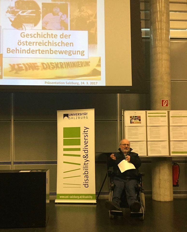 Volker Schönwiese spricht zum Publikum. Hinter ihm sieht man seine Powerpoint-Präsentation und ein Roll-Up des disability&diversity Zentrums Salzburg.