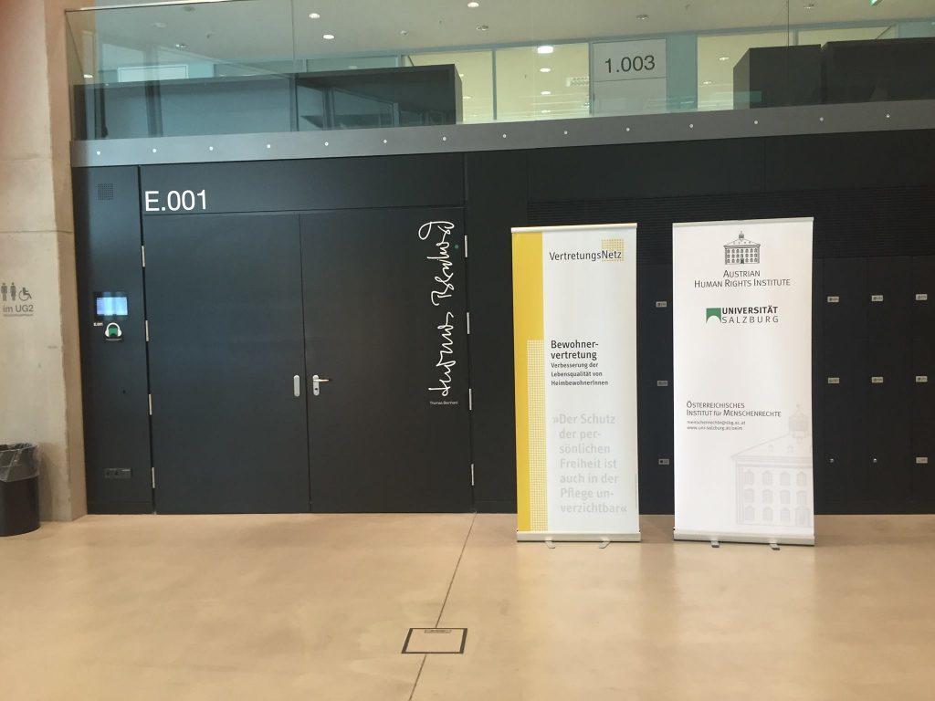 Der Hörsaal von außen. Daneben steht ein Roll-up von VertretungsNetz und ein Roll-up vom Österreichischen Institut für Menschenrechte.